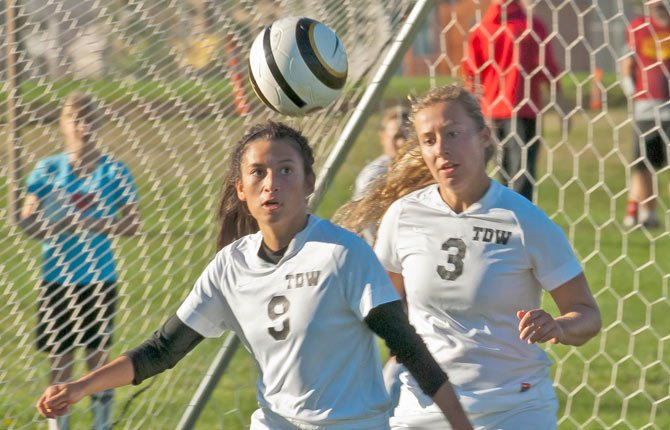 The Dalles Wahtonka junior defender Marta Gamez, left, and senior teammate Bailey Cordell converge to drive a loose ball away from the Eagle Indian goal during Tuesday's varsity soccer game against Hermiston in The Dalles. TDW built a 2-0 lead in the opening half, but the visiting Lady Bulldogs got a tying score in the 81st minute to salvage a 2-2 deadlock.