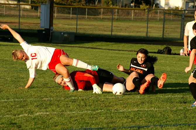 Columbia High forward Katherine Childs (no. 10) and Kalama defender Shelby Little are upended by Chinooks goalkeeper Holly Dye during a play on the ball in front of the Kalama goal last Thursday. The Bruins netted six goals in the Trico League match en route to their fifth consecutive win and sole possession of second place in Trico standings at 5-1. On Tuesday, the Bruins put their winning streak on the line against third-place La Center on the Wildcats' home pitch.