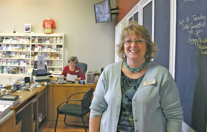 LISA FARQUHARSON, foreground, stands in the refreshed lobby of The Dalles Area Chamber of Commerce with longstanding employee Lois Hobbs at her desk and part of the expanded brochure space in the background.