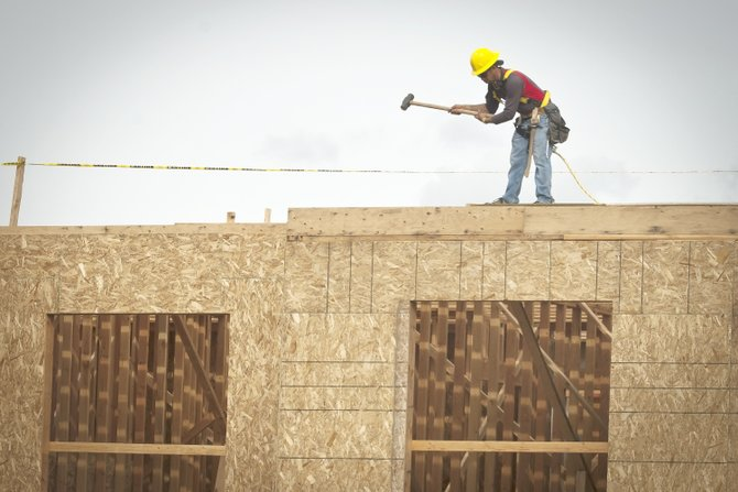 A construction worker bangs a sheet of plywood into place as he works on top of the Cousin's Country Inn expansion in The Dalles Wednesday, Oct. 2.
