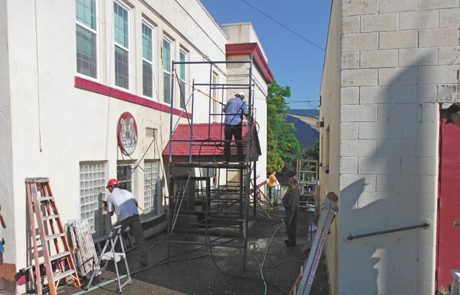 WORKERS ON SCAFFOLDING help clean the exterior of the Mosier Community School as part of the Church of Jesus Christ of Latter-day Saints annual Day of Service.    	Contributed photo