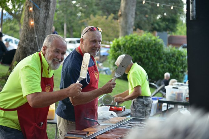 "VETERAN ""HASH SLINGERS"" Paul Zastrow, left, and Phil Hukari joke around as they flip burgers at Families in the Park in Jackson Park."