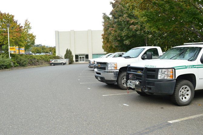 U.S. FOREST SERVICE trucks lie idle in the parking lot of the USDA, Columbia Gorge Scenic Area, and Forest Service building located on the east side of the Waucoma Center in downtown Hood River. On the other side of the parking lot, spaces normally filled with the personal vehicles of government workers are empty thanks to the government shutdown.