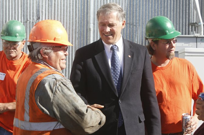 Mill worker Ron Bourgeau greets Gov. Jay Inslee on Monday, Oct. 7 at Omak Wood Products in Omak.