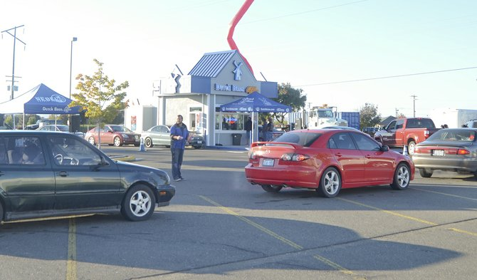 "Motorists line up while weaving their vehicles around the parking lot last Friday in anticipation of a free 16-ounce beverage at the newly opened Dutch Bros. Coffee shop at 2630 E. Yakima Valley Hwy. in Sunnyside. The shop was opened by Erin Bates. Broistas greeted customers as they lined up and a few vehicles had ""Godutch"" emblazoned on them. Dutch Bros. Sunnyside is open from 5 a.m. to 10 p.m. Sunday through Thursday and 5 a.m. to 11 p.m. on Fridays and Saturdays."