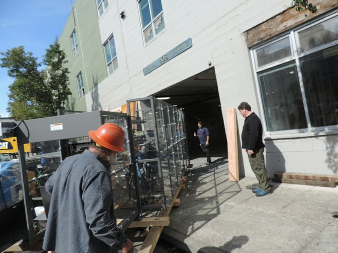 EXECUTIVE BREWER Jamie Emmerson, right, and brewmaster Jim Kelter, center, oversee arrival of the new box-making machine at the Columbia Street freight entrance on Sept. 24. The machine takes cardboard off pallets and erects and glues the bottom of the cartons, which then hold six-pack containers. Steering is Nick Linebarger of Honald Crane in The Dalles.