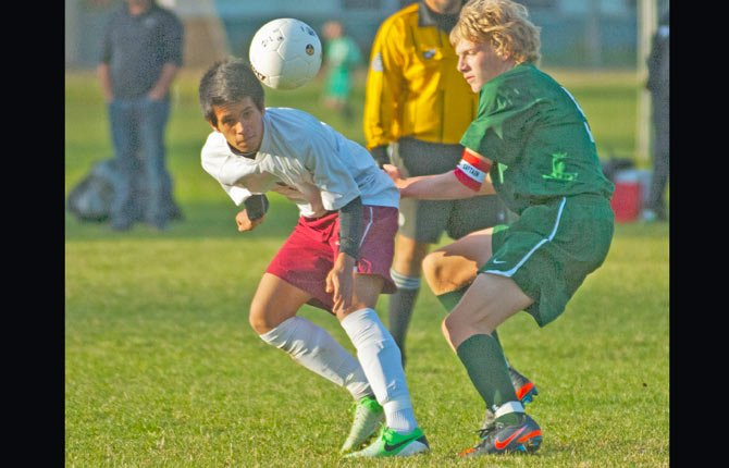 The Dalles Wahtonka sophomore Leo Hernandez, left, makes a low head pass downfield around Riley Kendrick of Pendleton in Tuesday's Columbia River Conference boy's soccer match in The Dalles. In the game, TDW broke open a 1-1 tie with goals by Andres Manzo and Leo Hernandez to upend the Buckaroos.