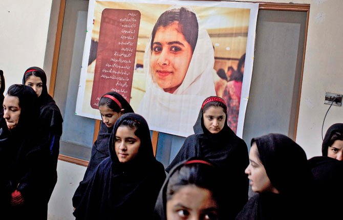 PAKISTANI GIRLS gather under a poster of Malala Yousufzai in her old school in Mingora, Swat Valley, Pakistan. The giant poster of her that once emblazoned the wall of the assembly hall has been removed. The school made no plans to recognize the anniversary of Malala's shooting by Taliban, teachers and students are afraid.