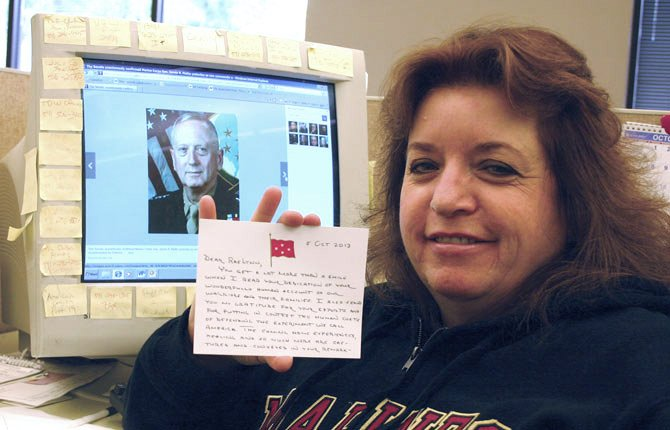 RAELYNN RICARTE holds the note she received Oct. 10 from retired U.S. Marine Corps Gen. James Mattis, who is pictured on the computer monitor in the background. Mattis served as the 11th Commander of the United States Central Command, overseeing the wars in Iraq and Afghanistan, where Ricarte's son served.
