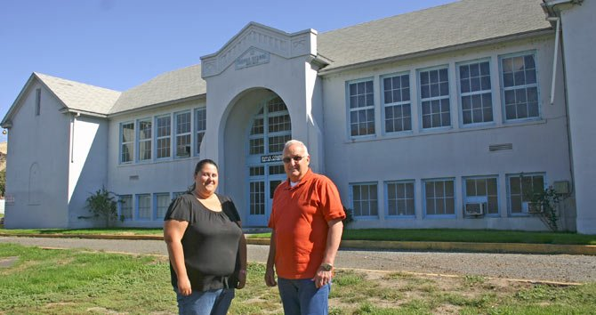 JACLYN McCURDY and Cliff Jett, city administrator and mayor of Rufus, stand in front of the old Rufus School, which they envision as a future community center and renewable energy interpretive center, one of several local projects they hope will bring new residents and new commerce to their Sherman County town.
