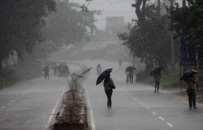 Indians hold umbrellas as they head to a cyclone shelter in  Chatrapur in Ganjam district, India, Oct. 12. Strong winds and heavy rains pounded India's eastern coastline Saturday, as hundreds of thousands of people took shelter from a massive, powerful Cyclone Phailin expected to reach land in a few hours.