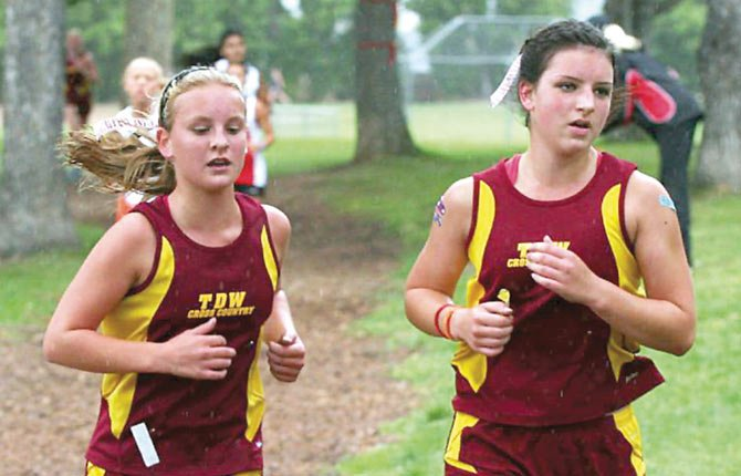 THE DALLES WAHTONKA cross country runners Luisa Meyer (left) and Kellina Coy strut their way through the Sorosis Course in a race held earlier this season. In all, the Tribe had 20 participants set personal records.