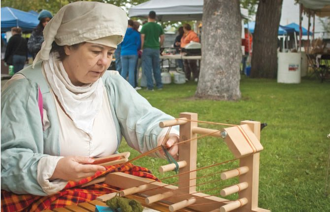 "Jaqueline de Lioncourt (Jennifer Berry of Portland) works a Inkle Loom based on those used in the Middle Ages. The loom was used to create narrow work: Belts, trim and bag handles, for example. She was at City Park in The Dalles Oct. 12, as part of a ""History Lives"" presentation by The Society for Creative Anachronism, which demonstrates and studies life from 600 to 1600 A.D."