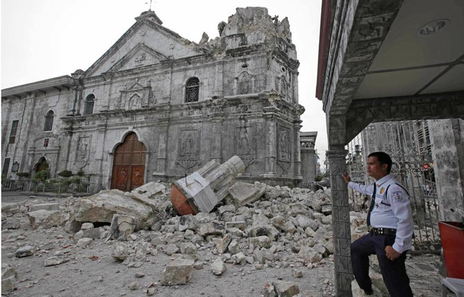 A private guard stands near the damaged Basilica of the Holy Child following a 7.2 magnitude earthquake that toppled the bell tower of the Philippines' oldest church Tuesday, Oct. 15.