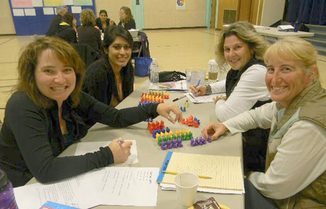 "TEACHERS (from left) Kim Granville (Dry Hollow), Nanci Vera (Oregon Child Development Coalition), Ronda Hull (Mid-Columbia Children's Council) and Dawn Pounders (Great and Small Child Development Center) work on building classroom strategies together at Friday's ""It All Adds Up"" training."