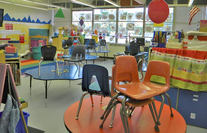 This dry hollow KINDERGARTEN CLASSROOM may be empty of students, but it's stuffed full of chairs and classroom equipment, leaving little room to move between tables, cubbies and painting easels.