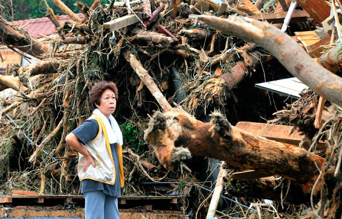 A woman looks at the aftermath of landslides in the rubble of smashed houses in Oshima after a powerful typhoon hit Izu Oshima island, about 75 miles south of Tokyo Wednesday morning, Oct. 16.