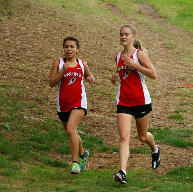 Melissa Fortanel (left) and Leslie Nuckoles run side by side, stride for stride, last Wednesday during a Trico League meet hosted by Columbia High at Husum Hills Golf Course. The CHS girls and boys teams won their respective meets. On Oct. 23, CHS will host the Trico League Championships at Husum Hills.