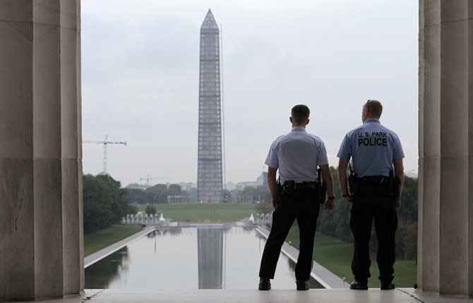 WITH the Washington Monument in the distance, Park Service police officers stand on duty at the Lincoln Memorial in Washington, Thursday, Oct. 17. Barriers went down at National Park Service sites and thousands of furloughed federal workers began returning to work throughout the country Thursday after 16 days off the job because of the partial government shutdown.