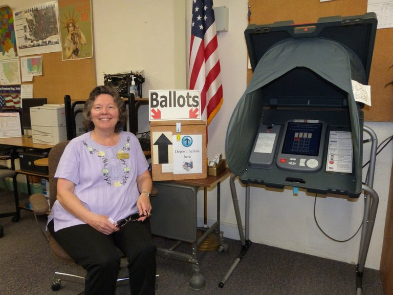 Okanogan County Elections Administrator Mila Jury poses with the ballot box in the Okanogan County Courthouse on Friday as voting for the Nov. 5 election begins.