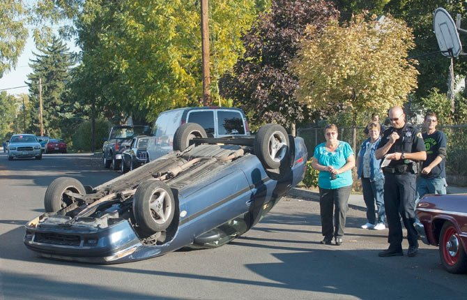 A blue sports car sits on its top after striking a parked car and rolling over in the 1000 block of East 8th in The Dalles Thursday afternoon. No one was injured in the single vehicle accident. 	Mark B. Gibson photo