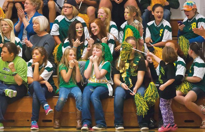 Sporting various shades of green, South Wasco County fans watch the action as the Redsides volleyball team takes on Dufur Thursday, Oct. 17 in Maupin.