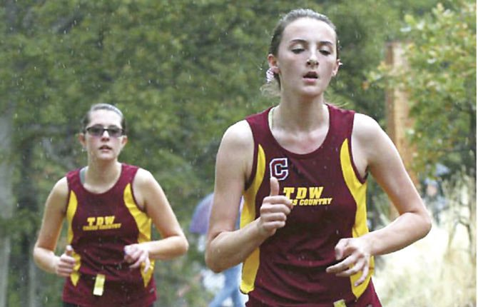 TDW'S Maddie Wood (front) and Emily Morin stride home at the Nelson Invite this season. In Pendleton Friday, Morin finished fourth in 19 minutes and 55.22 seconds, while Wood came in seventh.