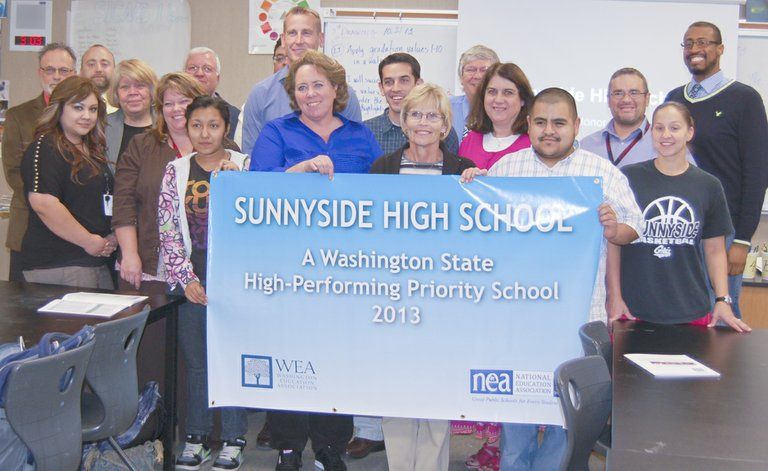 "Representatives of the Sunnyside High School staff and school board celebrate the success of the three-year school improvement grant. Washington state schools outperformed the rest of the nation in reading and writing improvements while using the grants. Sunnyside's dramatic improvement in graduation rates was also singled out by Stephen Miller, vice president of WEA, when he presented a banner to the school in honor of its accomplishments. ""Nobody has done that in 10 years, never mind four years,"" he said of Sunnyside's jump from 49 percent graduation to 85 percent graduation. Miller is urging people to write to state representatives to let them know what local control of school funding is capable of achieving."