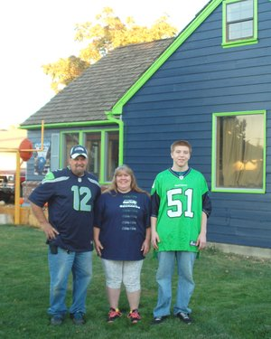 Wearing their Seahawk gear in front of their Seahawk house are (L-R) Brad Denson, Wendy Denson and Andrew Wolf.