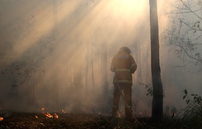 A firefighter mops up after a firestorm swept through a property in Bilpin, 75 kilometers (47 miles) from Sydney Oct. 23. Scores of Australians evacuated their homes in mountains west of Sydney on Wednesday as intensifying winds fanned wildfires and grounded the helicopters that were fighting them.