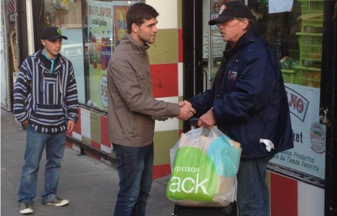 ODY PARKER, foreground, shakes hands with a man in the Tenderloin District of San Francisco as student Dustin Whitmire looks on.