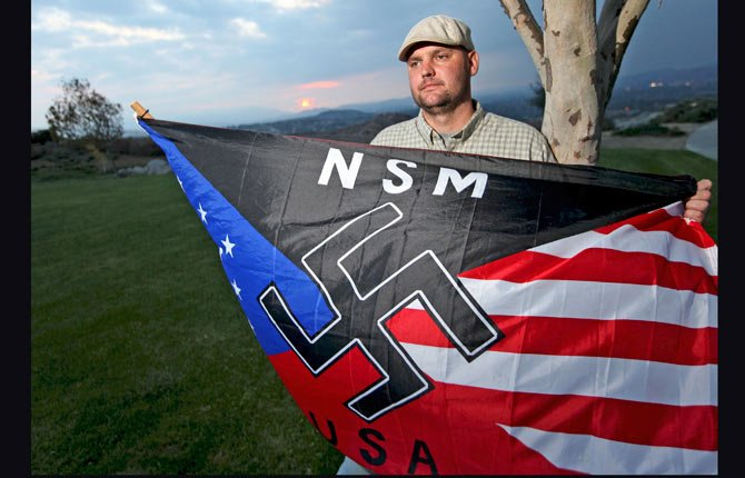 In this Oct. 22, 2010 file photo, Jeff Hall, who was killed by his son, holds a Neo Nazi flag while standing at Sycamore Highlands Park near his home in Riverside, Calif. On Friday Oct. 25, 2013 a judge will to determine where Hall's son will spend his teens and, possibly, his early adult years. The judge hearing the case in Riverside County must decide not how to punish a child for second-degree murder, but how to rehabilitate someone who grew up in an abusive home.