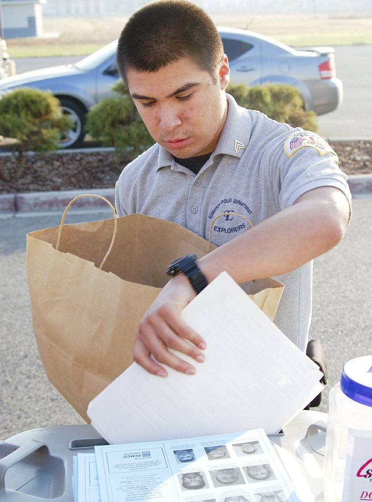 Sunnyside Police Explorer Joaquin Bustamante (at right) drops documents to be shredded into a locked bin during the Yakima County Crime Stoppers event this past Saturday in Sunnyside. Police explorers and volunteers from Bank of America helped unload boxes of documents from cars to place in the locked bins for shredding at a later date. The event had stations open around the county and also accepted expired prescription drugs. In Sunnyside, six bins of documents and one large bag of medication were collected and about $120 was donated to Crime Stoppers. Across the county the event brought in 55 bins of items to shred, nine large bags of drugs and $1,850 in donations toward Crime Stoppers.