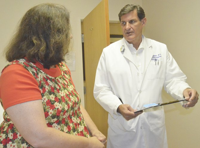 Dr. David Shoemaker discusses with Sandra Linde symptoms she has been experiencing with her leg. Shoemaker works at Sunnyside's Specialty Center Surgical Group as a vascular surgeon.