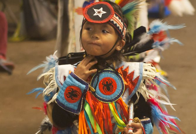 A YOUNG dancer adjusts his chin strap during a dance at the Celilo Pow Wow Sunday, Oct. 27. The gathering took place in their village east of The Dalles.  	Mark B. Gibson photo.