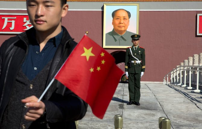 A tourist holds up a Chinese flag as he poses for photos near a Chinese paramilitary policeman on duty in front of former Chinese leader Mao Zedong's portrait on Tiananmen Gate, close to the site of an incident Monday where a car plowed through a crowd before it crashed and burned in Beijing, China, Tuesday, Oct. 29.