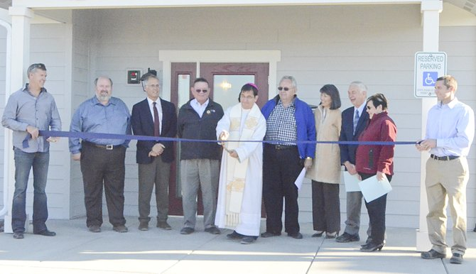 Celebrating the completion of Sor Juana Ines Court in Grandview with a ribbon cutting are (L-R) Mark Ludgren, Mayor Norm Childress, Yakima County Commissioner Kevin Bouchey, Rep. John McCoy, Bishop Joseph J. Tyson, former Rep. Norm Johnson, Rep. Sharon Tomiko Santos, former Governor Mike Lowry, Rep. Sherry Appleton and Justin Bates.