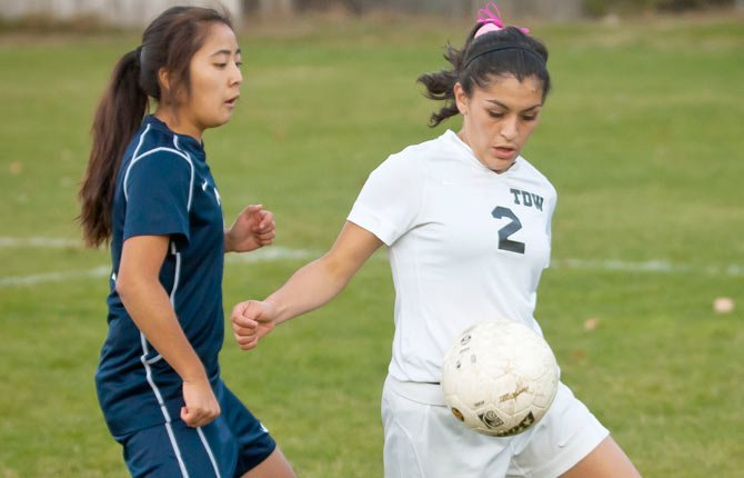 The Dalles Wahtonka sophomore Monique Mendiola (right) strives to pull the ball away from a tough Hood River defender during Tuesday's girl's soccer game in The Dalles. HRV won the game, 3-1.