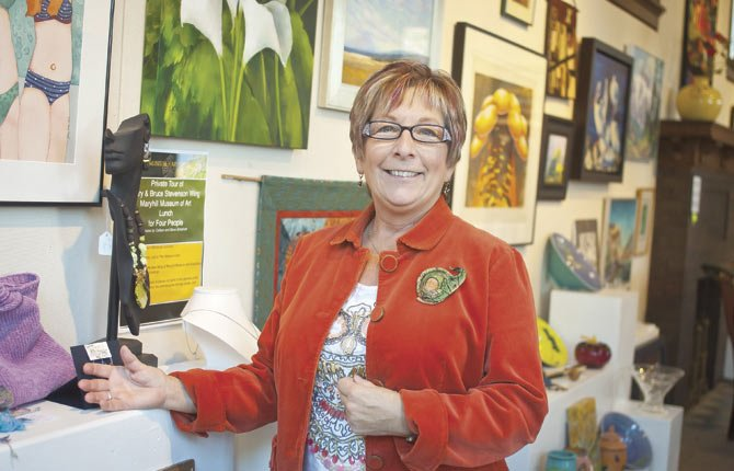 A wall of art, pictured here behind The Dalles Art Association Executive Director Carmen Toll, will be auctioned to the highest bidder Saturday, Nov. 2, in the 56th annual art auction in the Civic Auditorium Ballroom.