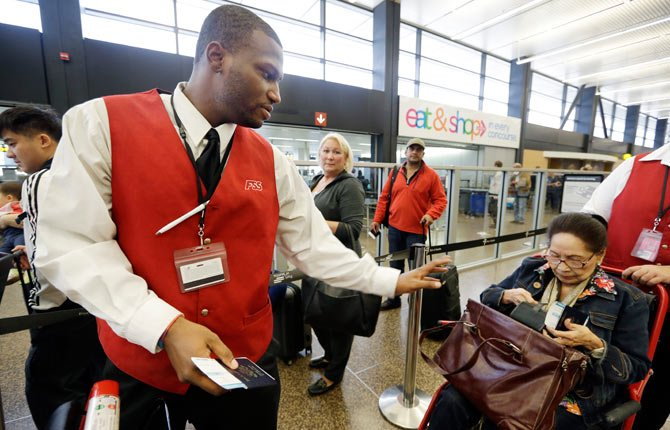Wheelchair attendant Erick Conley, left, assists an elderly passenger heading overseas Oct. 22 at Seattle-Tacoma International Airport in SeaTac, Wash. There's a campaign underway to raise the minimum wage to $15 for the more than 6,300 jobs at Seattle's largest airport. If approved by voters on Nov. 5, the wage rate, as well as sick days and other benefits, would only apply to the city of SeaTac. The vote is one of the latest flashpoints in the national debate over the minimum wage after fast food workers and others held a series of summertime rallies to bring attention to their struggle to earn a living.