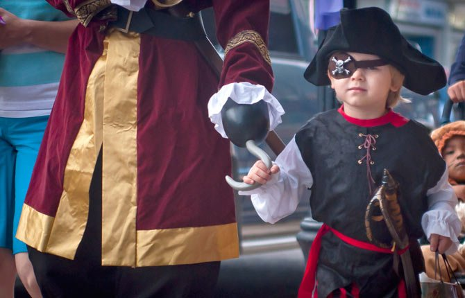 PIRATE Xander Kramer, 4, above, keeps a tight hold on his captain's hook (his dad, Justin Kramer) as they navigate crowded Second Street to trick-or-treat for Halloween.