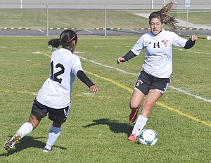 Sunnyside's Jordan Rodriguez (R) maintains possession of the ball in Kennewick territory as teammate Emilee Maldonado hustles to help.