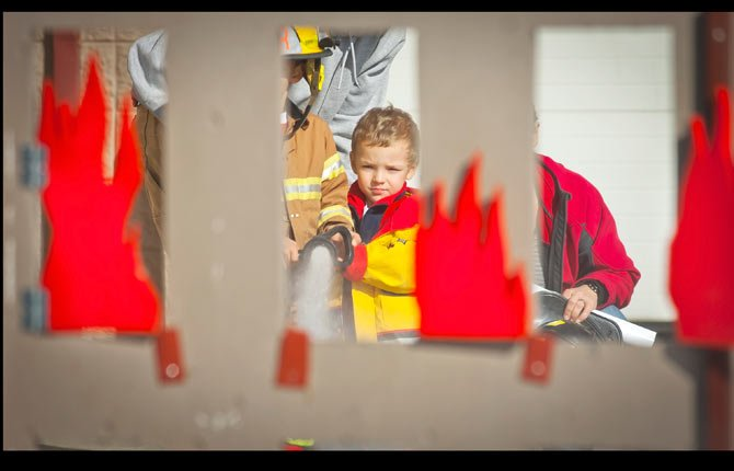 "Kellen Hutchison blasts ""flame"" from a series of windows with a fire hose, helped by his brother Jake, during an open house at Mid-Columbia Fire and Rescue Nov. 2."