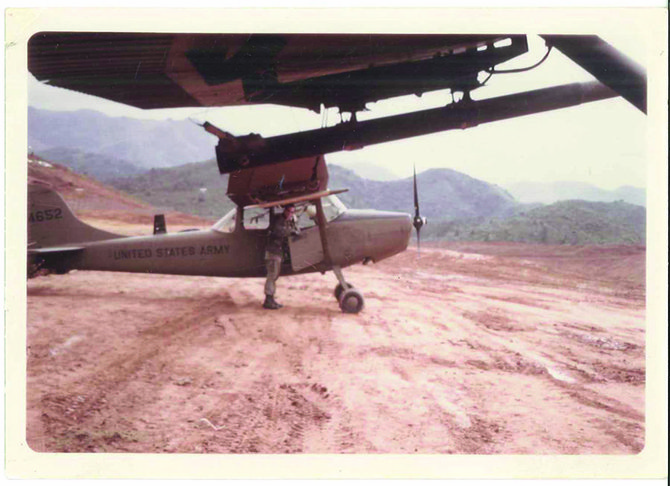 "LARRY DEIBERT with his plane, in Vietnam c. 1967: ""Our air speed was about 95 mph. Every time we were supporting American troops in contact with the enemy, we would receive small arms fire, .51 cal-iber anti-aircraft and fire from 37mm and 81mm air bursts . . ."""