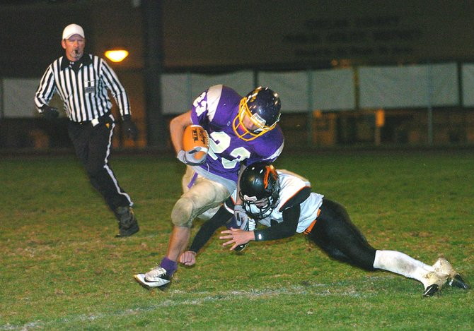 Carlos Cruz of Pateros gets hit by an Entiat defender during an outside sweep in football action Tuesday night in Chelan. Okanogan County official Rick Duck follows the play.