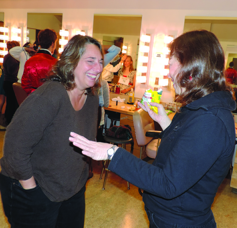 Costume leads Karin Tauscher and Kathy Peldyak share a joke in the green room as Peldyak holds a bag of the telltale cough drops.