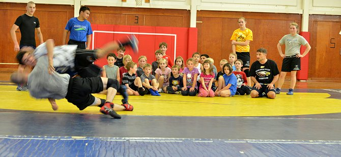 YOUTH WRESTLING is gearing up for the season. Pictured here are HRVHS wrestlers Christian Marquez and Andrew DeHart giving a recent demonstration to May Street students, with coach Trent Kroll giving a play-by-play and Kyle Weseman, James Estes, Payton Rigert and Jessica DeHart helping.