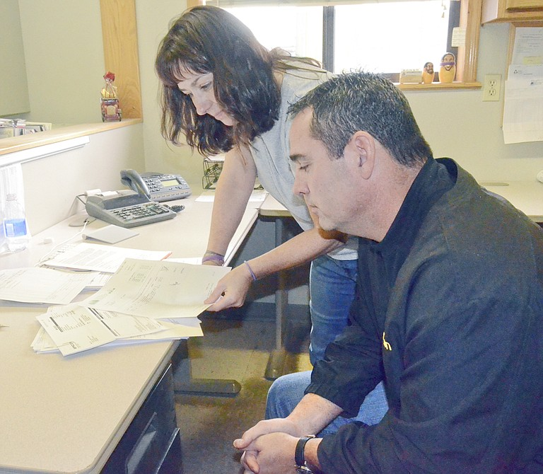 Tracy Kaufman and her brother, Eric Swinehart, at Sunnyside's Bi-Rite Lumber review a customer's bill.