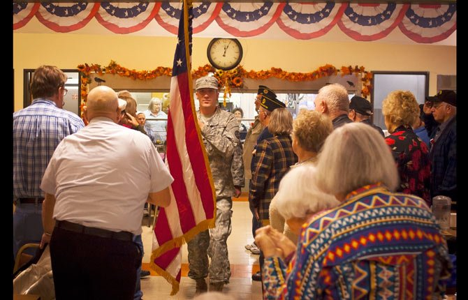 National Guard soldiers Zachary Parsons, followed by William Sherburne, present the flag as seniors gather for a meal in honor of Veterans at the Mid Columbia Senior Center in The Dalles Thursday, Nov. 7.
