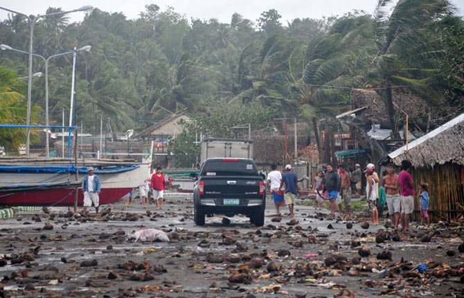 Debris litters the road by the coastal village in Legazpi city following a storm surge brought about by powerful Typhoon Haiyan in Albay province Nov. 8 about 520 kilometers ( 325 miles) south of Manila, Philippines.